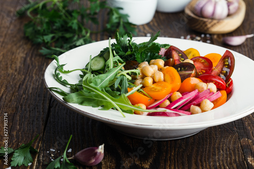 Obraz na plátně  Veggie chickpeas salad with fresh vegetables and herbs, plant based meal
