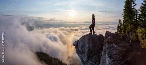 Fototapeta Adventurous Female Hiker on top of a mountain covered in clouds during a vibrant summer sunset. Taken on top of St Mark's Summit, West Vancouver, British Columbia, Canada. obraz