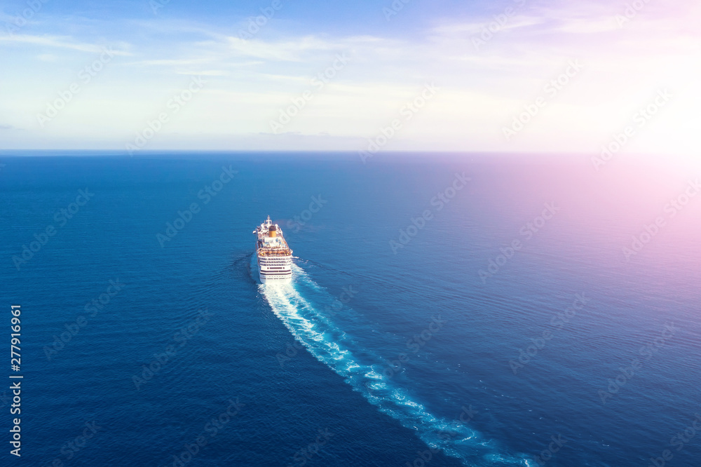 Fototapety, obrazy: Cruise ship liner goes into horizon the blue sea leaving a plume on the surface of the water seascape during sunrise. Aerial view, concept of sea travel, cruises.