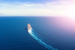 canvas print picture - Cruise ship liner goes into horizon the blue sea leaving a plume on the surface of the water seascape during sunrise. Aerial view, concept of sea travel, cruises.