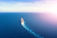 Cruise Ship Liner Goes Into Horizon The Blue Sea Leaving A Plume On The Surface Of The Water Seascape During Sunrise. Aerial View, Concept Of Sea Travel, Cruises.