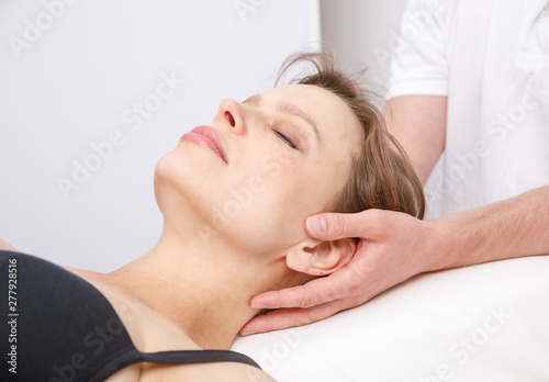 Woman receiving osteopathic treatment of her neck Canvas Print
