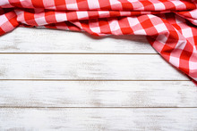 A Checked Gingham Picnic Tablecloth On Old Wooden Table Top View