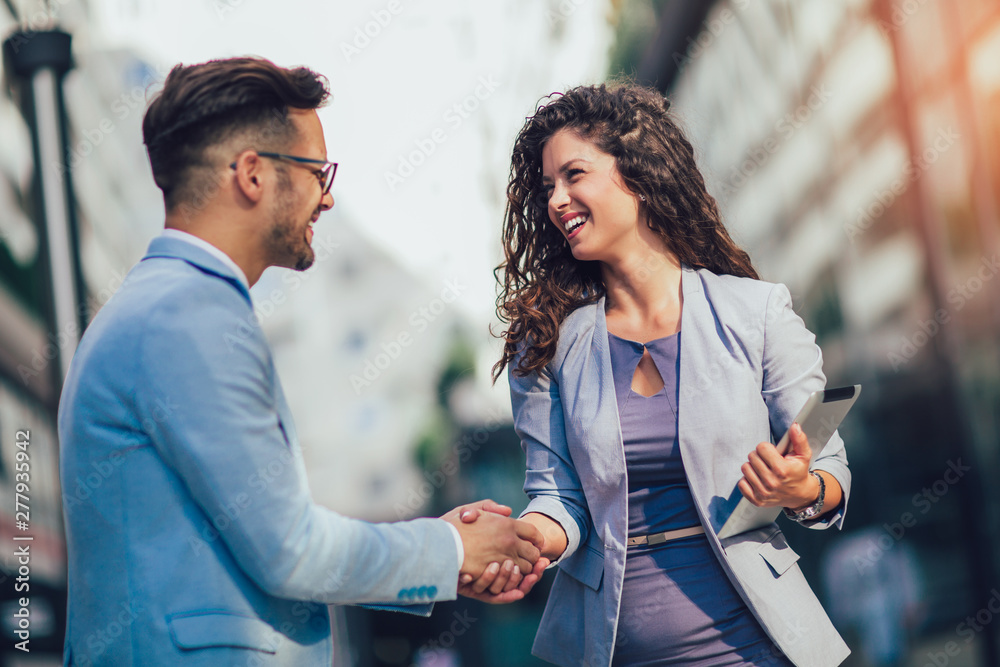Fototapeta Smiling business colleagues greeting each other outdoors