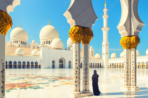 Tourist woman in traditional abaya dress inside Sheikh Zayed Mosque in Abu Dhabi, United Arab Emirates