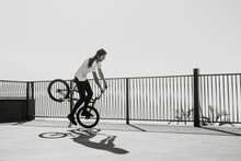 A Man Doing A Trick With His Bmx Bike In A Square