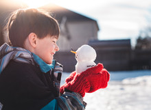 Young Boy Smiling At A Tiny Snowman That He's Holding In His Hands.