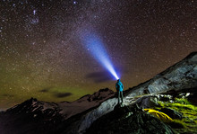 Figure Pointing A Light Towards The Nighttime Sky Filled With Stars
