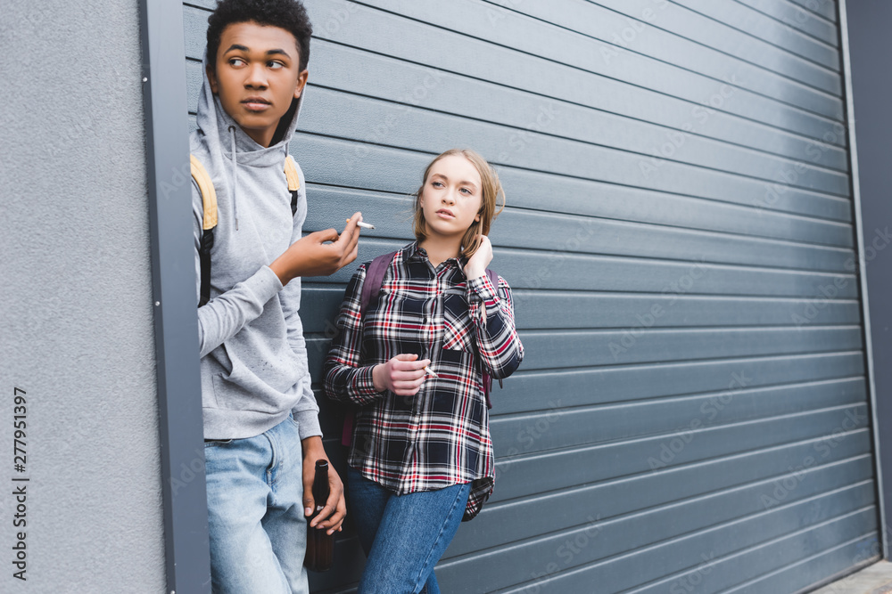 Fototapety, obrazy: african american boy and blonde teenager looking away, smoking cigarettes and holding beer