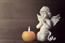 Angel And Candle On Dark Backg...