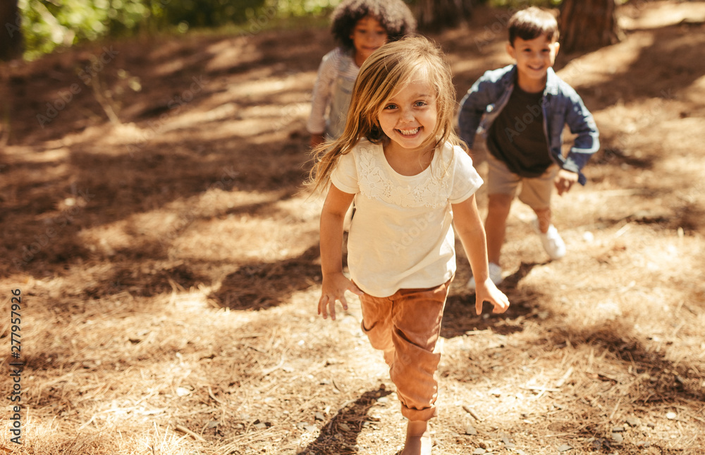 Fototapeta Cute girl running up hill in a park with friends