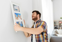 Interior Decoration And Renovation Concept - Smiling Man Hanging Picture In Frame To Wall At Home