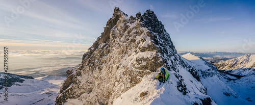 An epic panorama view of a mountainer or climber and his tent in a winter alpine mountain landscape Wallpaper Mural