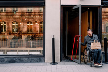 Man In Wheelchair With Shopping Bag Leaving Store
