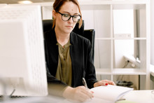 Mid Adult Female Sales Manager Writing On Book At Desk In Office
