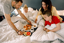 Father Serving Breakfast For Family On Bed In Hotel Room