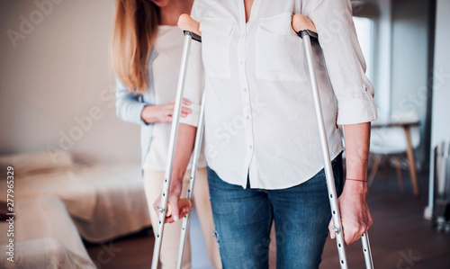 Daughter helping her mother to walk with crutches - Buy this