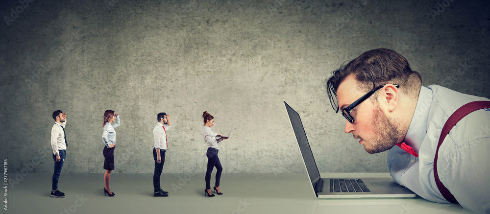 Fototapety, obrazy: Curious businessman looking at laptop analyzing group of businesspeople applying online for a job