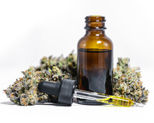 CBD Hemp Oil With Marijuana Buds On White Background
