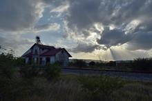 Vieja Estación De Tren Junto A Los Rieles En Un Día Nublado Con Los Rayos Del Sol Atravesando Las Nubes.