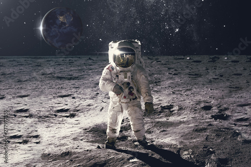 Fotografie, Obraz  Astronaut on rock surface with space background
