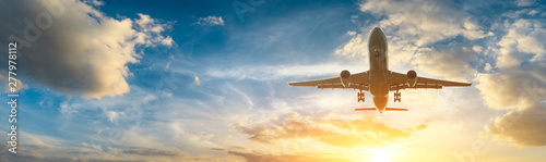 Airplane in the sky at sunrise Fototapeta