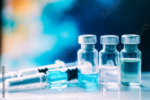 Photo Injectable medications in sealed vials and a disposable plastic medical syringe