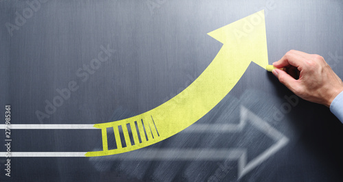 Obraz Changing business management concept. Businessman erasing white arrow and drawing yellow arrow on chalkboard. - fototapety do salonu