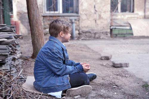 Valokuvatapetti Homeless little boy sitting outdoors