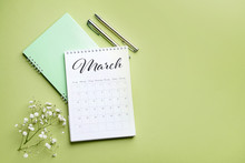 Flip Paper Calendar, Notebook And Flowers On Color Background