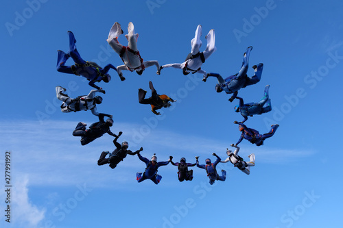 Slika na platnu Formation skydiving. A group of skydivers is in the amazing sky.