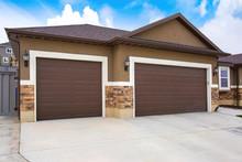 Exterior Of A Home With Two Brown Garage Doors Against Cloudy Blue Sky
