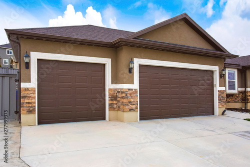 Exterior of a home with two brown garage doors against cloudy blue sky Wallpaper Mural