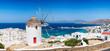 canvas print picture - Blick über die Stadt und den Hafen der Insel Mykonos im Sommer mit traditioneller Windmühle und weißgewaschenen Häusern, Kykladen, Griechenland