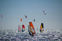 Windsurfers And Kiteboarders On Choppy Sea, In Backlight