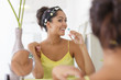 beautiful woman brushing her teeth in front of the mirror