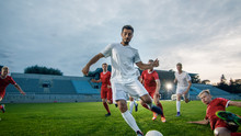 Professional Soccer Player Outruns Members Of Opposing Team And Kicks Ball To Score Goal. Soccer Championship On A Stadium.