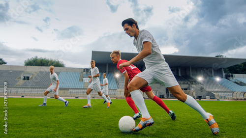 Fotografija  Professional Soccer Player Leads with a Ball, Masterfully Dribbling and Bypassing Sliding Tackles of His Opponents