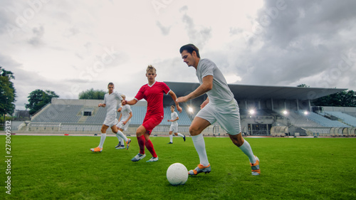 Photo  Professional Soccer Player Leads with a Ball, Masterfully Dribbling and Bypassing Sliding Tackles of His Opponents