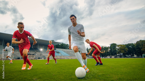 Fotografia, Obraz  Professional Soccer Player Leads with a Ball, Masterfully Dribbling and Bypassing Sliding Tackles of His Opponents