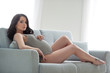 Leinwanddruck Bild - Pregnant girl woman brunette in a gray knitted body suit sitting on a cozy sofa in home interior. Pregnancy and maternity