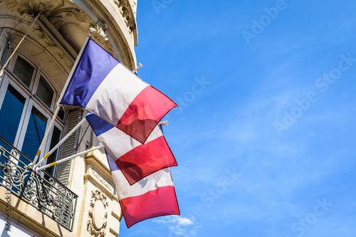 Low angle view of three french flags decking an haussmannian building in Paris, France, on a sunny summer day Canvas Print