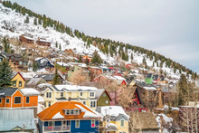Colorful Houses And Coniferous Trees On A Mountain Covered With Snow In Winter