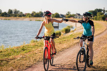 Women On Bike Riding By The Lake Shore Outdoors At The Park