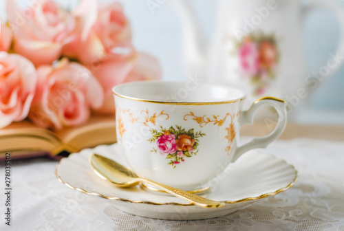 Fotomural Cup of tea with book, teapot and rose flowers on blue background with vintage to
