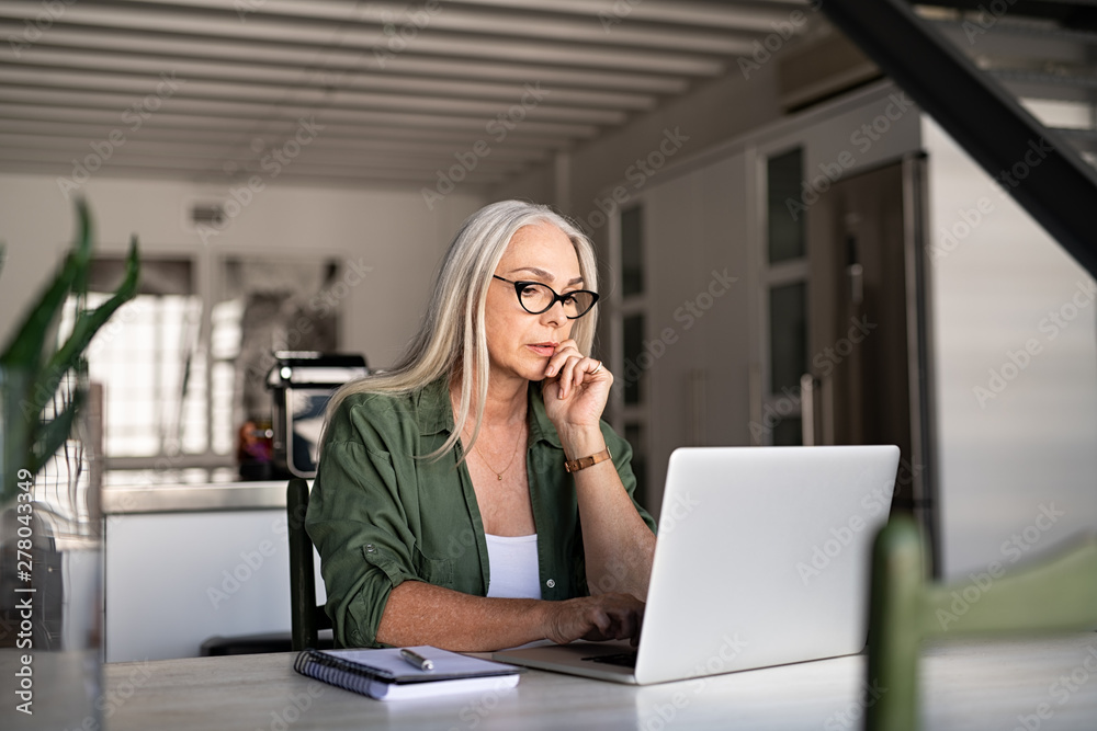 Fototapeta Worried senior woman using laptop