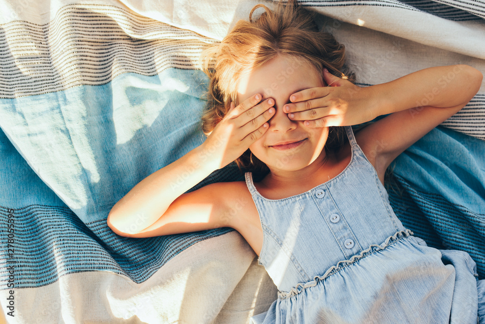 Fototapety, obrazy: Beautiful blonde little girl lying on the blanket, cover her eyes from the sun with both hands, enjoying summer day. Adorable child having fun and plaiyng peekaboo outdoors in the park