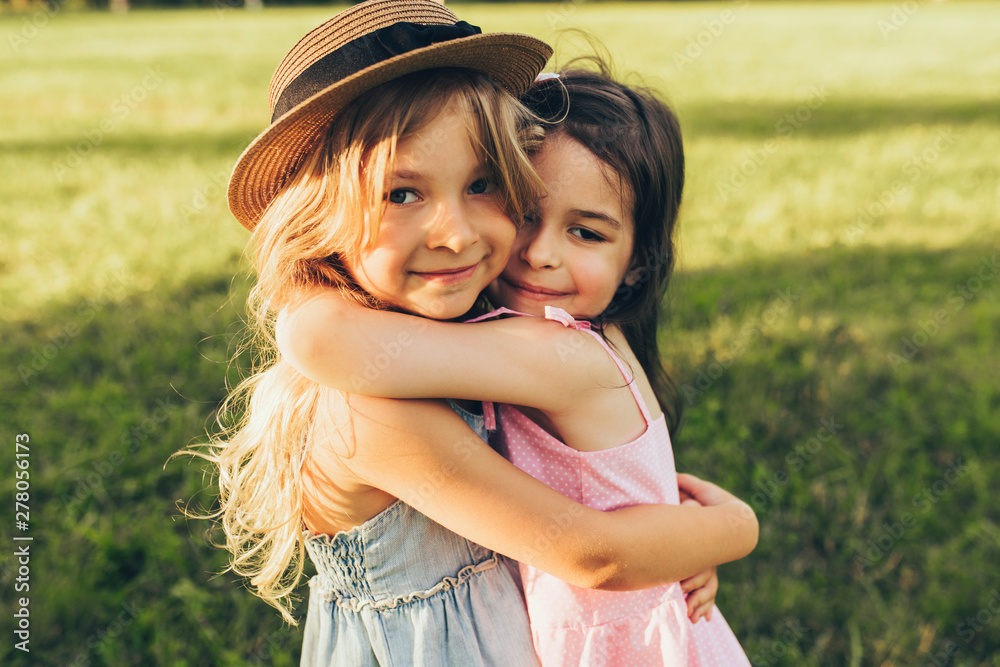 Fototapety, obrazy: Outdoors portrait of two adorable children shares love and frienship. Two little girls playing in the park. Two sisters having fun on sunlight and nature background. Childhood and friendship concept