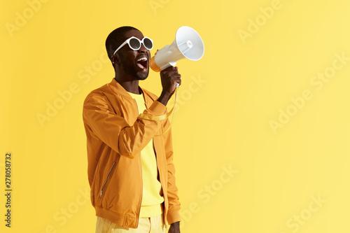 Photo Advertising. Man screaming announcement in megaphone portrait