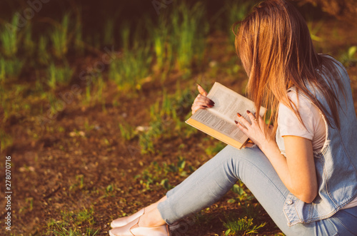 Deurstickers Young woman reading a book in the Park at sunset